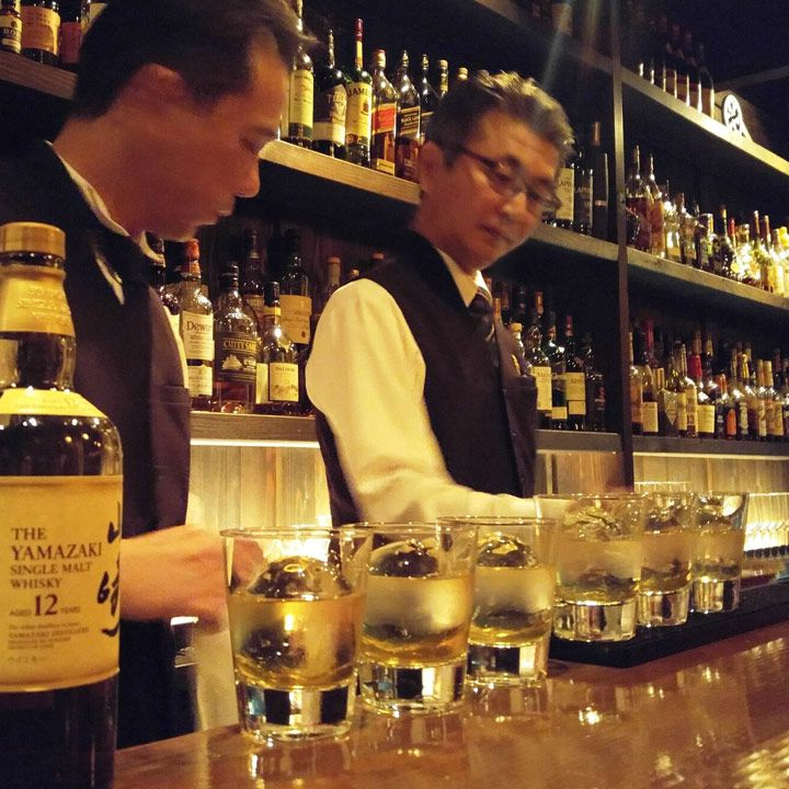The Door in Kyoto. A line of glasses filled with ice and water are chilling and two bartenders in dark vests are set to go to work.