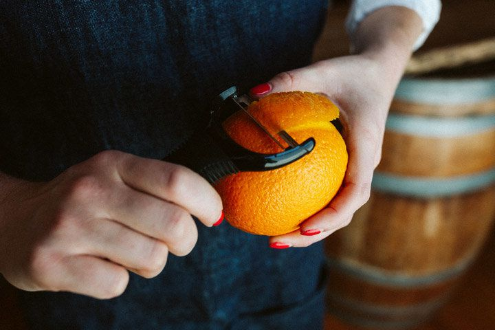 Using a wide peeler, a pair of hands with painted nails removed a large swath of peel from an orange
