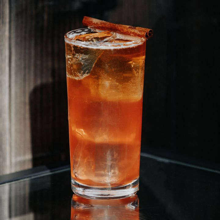 reddish-brown Ruby Hearts cocktail in a Collins glass, garnished with a cinnamon stick balanced on the rim of the glass