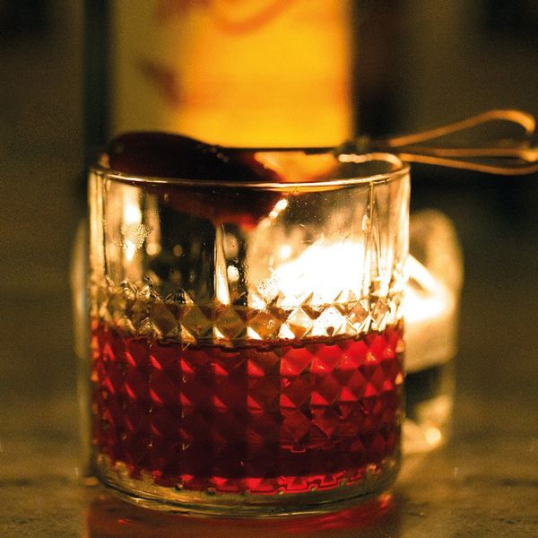 A faceted rocks glass sits on a bar top in front of a candle which illuminates the vivid red drink within. The glass is garnished with a Medjool date on a skewer.