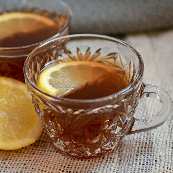 Two little glass mugs with small handles sit on burlap next to a lemon wedge. Both glasses are filled with a dark punch and garnished with a lemon slice.