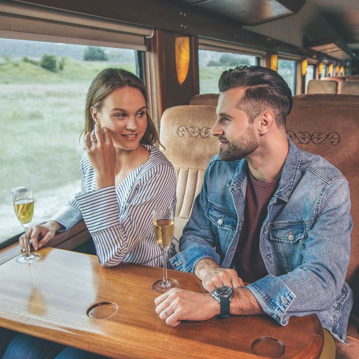 Jose Cuervo Express Train. A woman and a man are holding flutes and the vistas of tequila country are visible out their train-seat window
