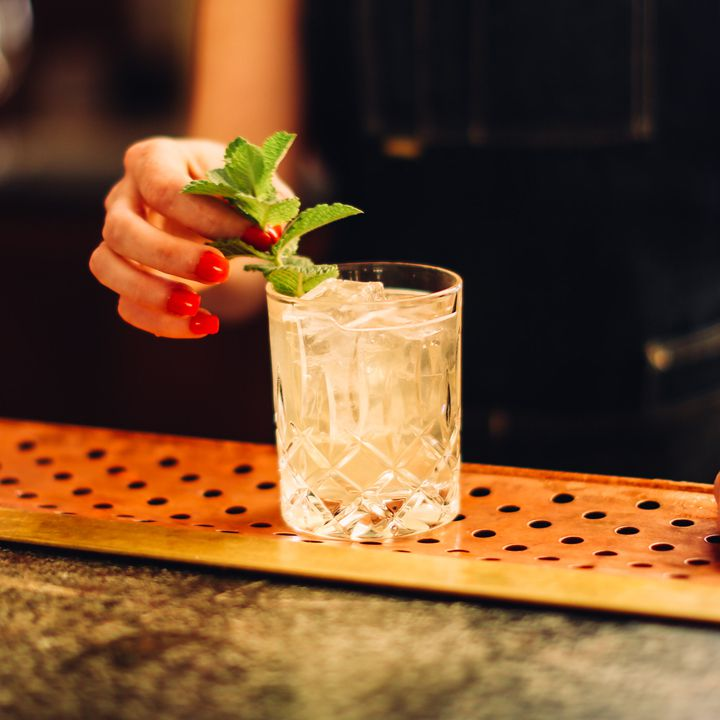 A hand with red nails garnishes a clear drink (A Rake's Bar's Better Late than Never) with a sprig of mint.