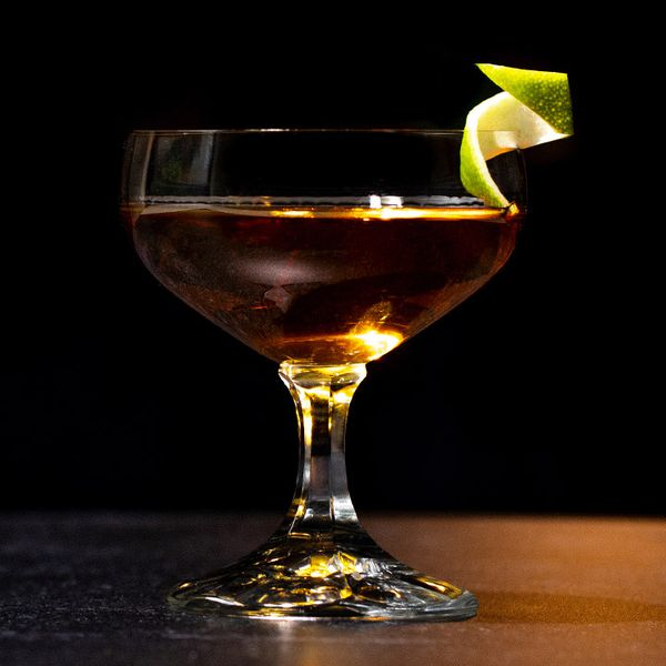 Distrito Federal, aka Tequila Manhattan, in a cocktail glass with a spiral lime twist garnish on the rim, served on a wooden surface