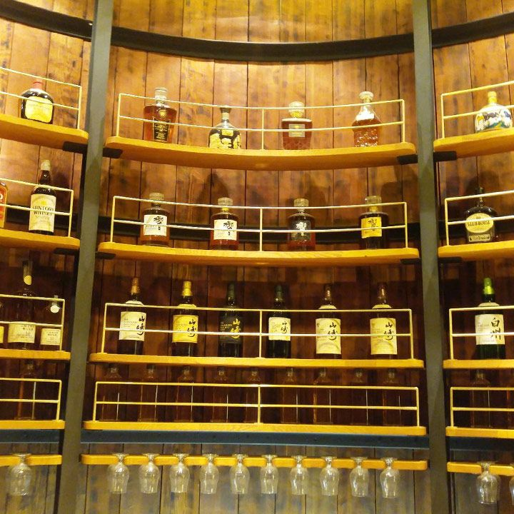 Yamazaki tasting room at Yamazaki Distillery. The varied expressions are housed on shelves behind thin gold barriers