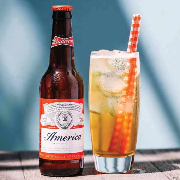 Big Red cocktail in a Collins glass over ice with two red-and-white straws, served next to a bottle of Budweiser