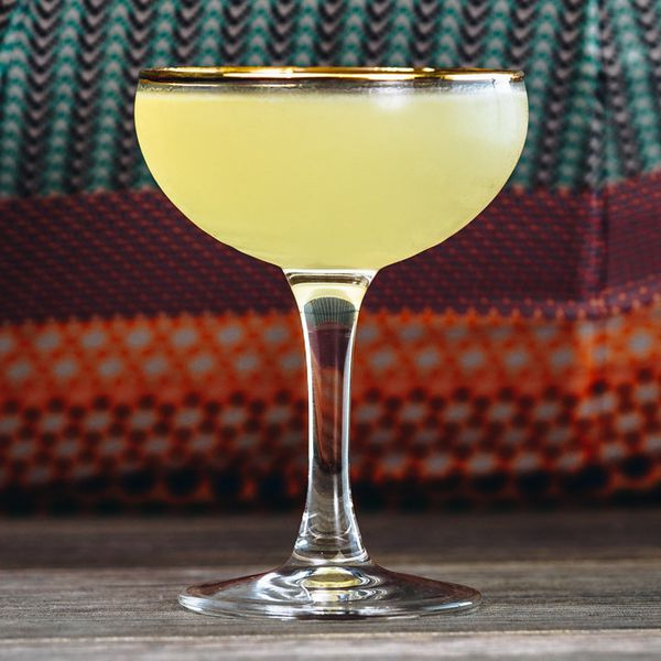 yellow-hued Evergreen Terrace cocktail in a gold-rimmed coupe glass