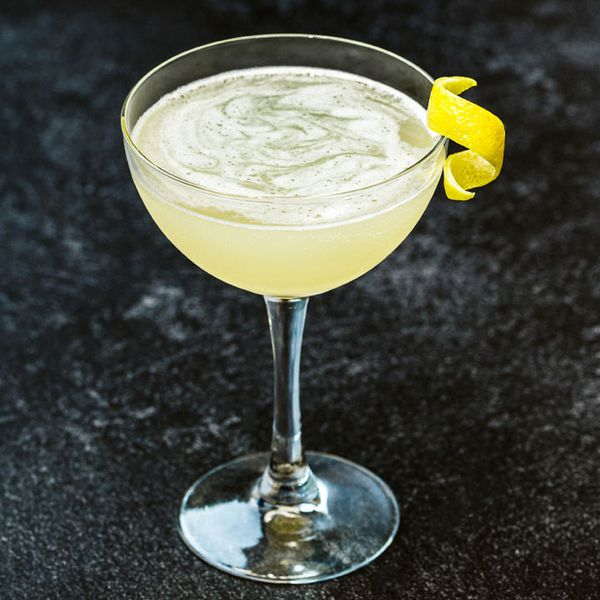 yellow-hued Necromancer cocktail in a coupe glass with a lemon twist garnish on the rim