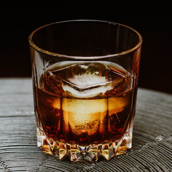 A chunky Old Fashioned glass rests on a ringed placemat. The drink within is a dark crimson, with one large square ice cube in it. The background of the image is solid black.