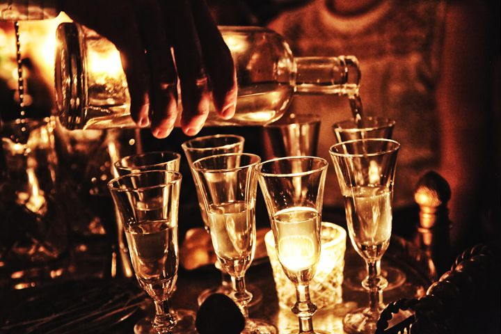 A dark, moody photo of a clear spirit being poured into cordial glasses