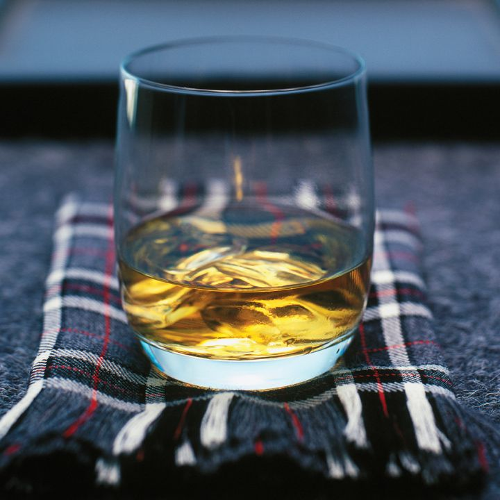 A short, curved glass with a dram of golden Canadian whiskey sits on a tartan scarf. The scarf is patterned with various shades of gray and lines of red.