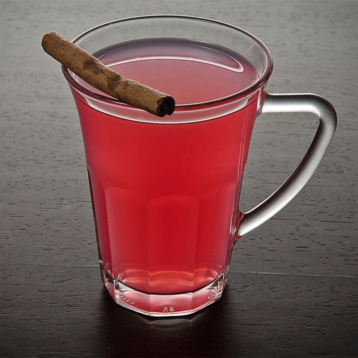 light red Francophile cocktail in a glass mug with handle, garnished with a cinnamon stick balanced on the rim