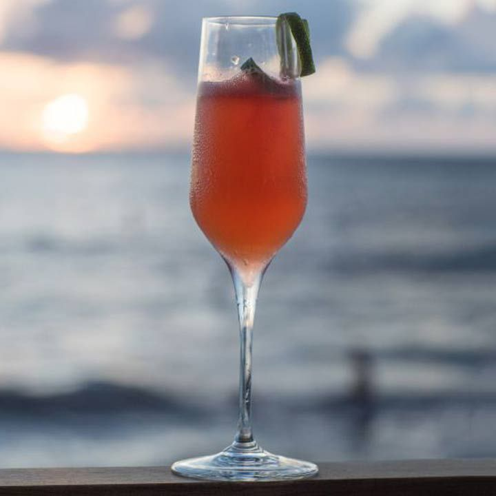 Pink cocktail in a champagne flute at Ave, in Grand Cayman, set against a sunset over water