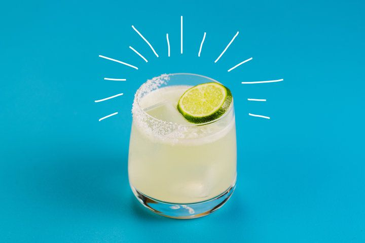 A spicy Margarita served in a clear rocks glass, rimmed with salt and garnished with a lime wheel