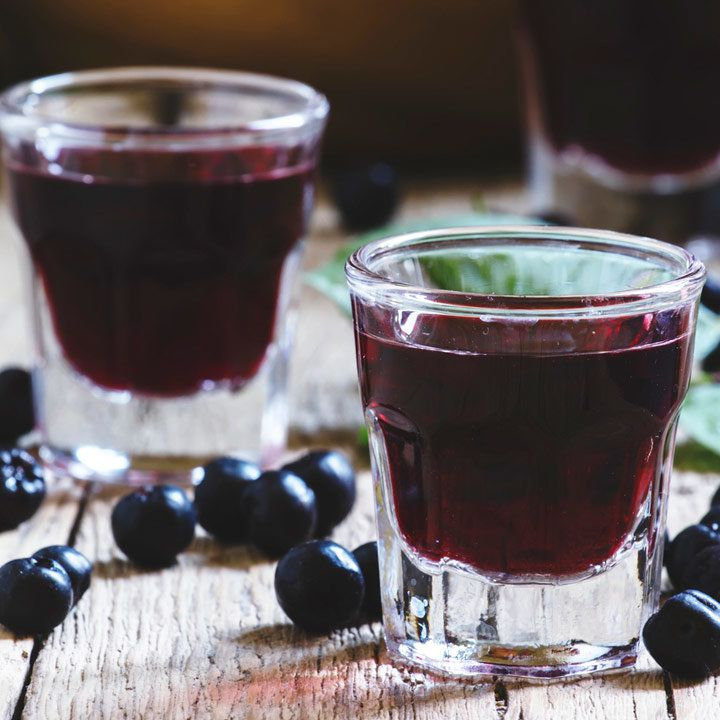 Two small clear glasses of deep red-purple mirto surrounded by ripe berries