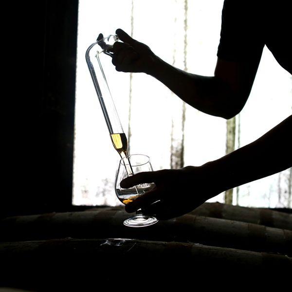 pulling rhum from a barrel at a distillery