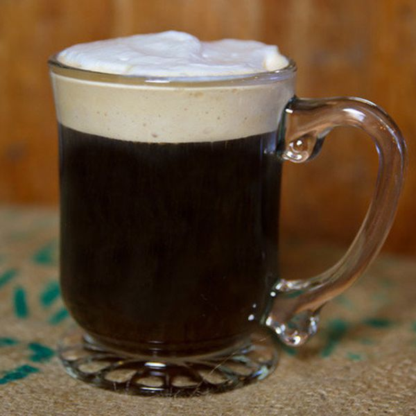 A clear mug is filled with a dark coffee, and topped with a thick white layer of foam. It rests on a tarp.