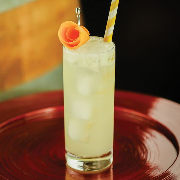 A highball glass rests on a shiny red plate. The glass holds a number of ice cubes and a light-gold highball. A yellow and white-striped straw extends from the drink, and it's garnished with a curled grapefruit peel held by a silver pick.