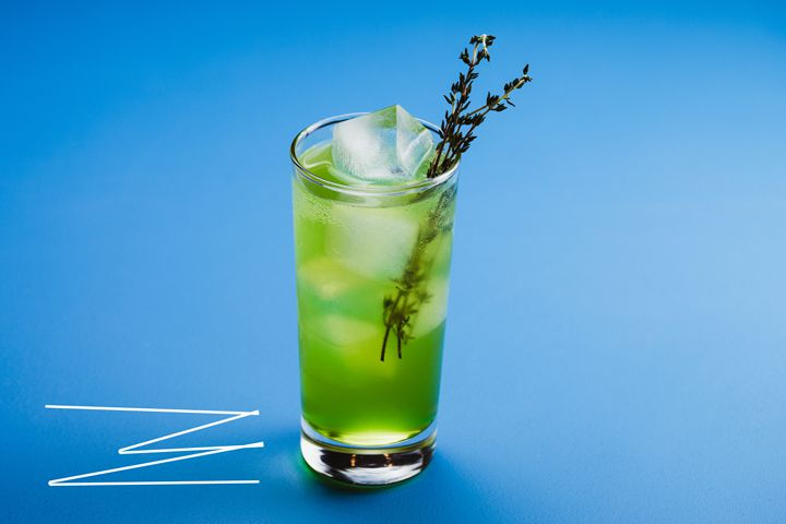 A tall, thin glass holds a few large ice cubes and an emerald green beverage, garnished with two sprigs of thyme. It sets on an all blue backdrop; adjacent are a few zig zagging white lines
