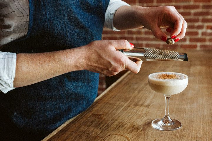 A woman wearing a navy apron is mostly out of the shot, except for her torso, arms, and hands, whose fingers are painted bright red. She grates a chunk of nutmeg over a frothy, light brown cocktail in a coupe glass.