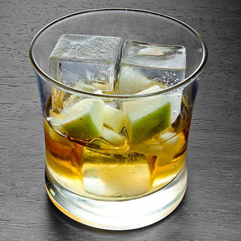 On a gray surface, a curved rocks glass with a tapered mouth holds three large ice cubes, a number of apple cubes, and some rye whiskey.