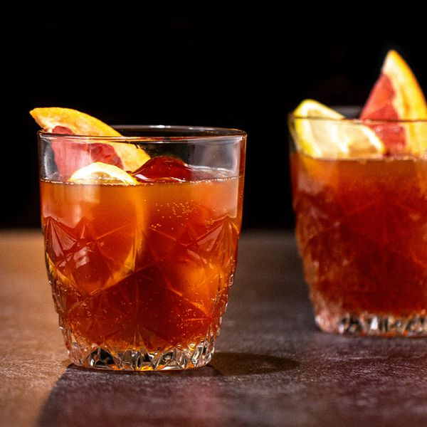 Two short punch glasses with intricate inlays rest on a granite bar top. They're both filled with large slices of lemon and grapefruit, some ice cubes, and a deep red punch.