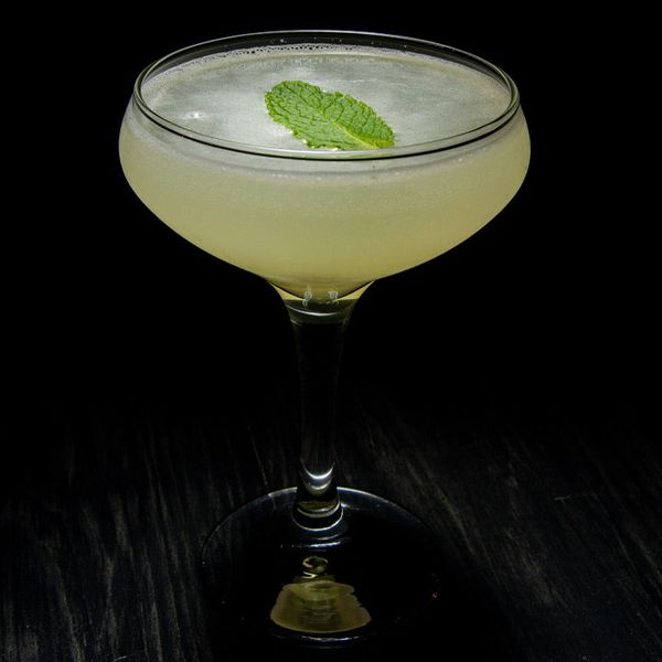 light green South Mint 75 cocktail in a coupe glass, garnished with a single mint leaf