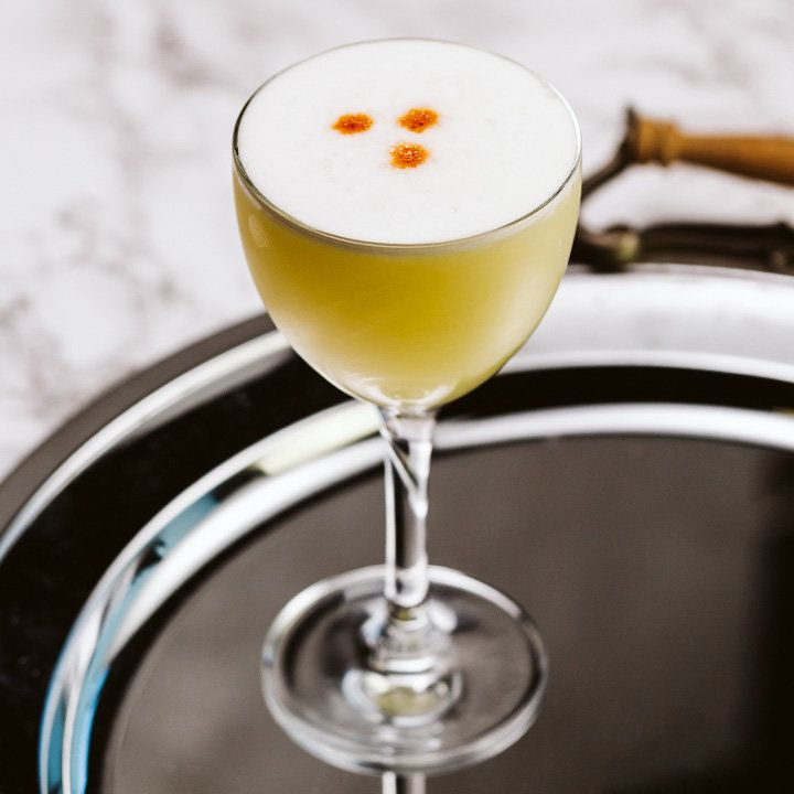 pisco sour cocktail with three drops of bitters on top, served on a silver tray