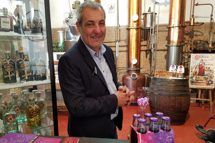 Carlo Pische stands in his mirto distillery in front of a glass case of bottles