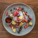 A plate of cinnamon French toast and fresh fruit dusted with powdered sugar