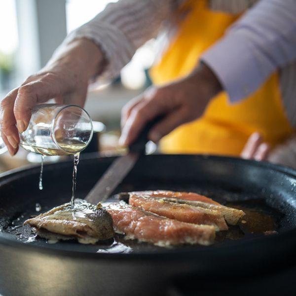 woman adding white wine while preparing fish