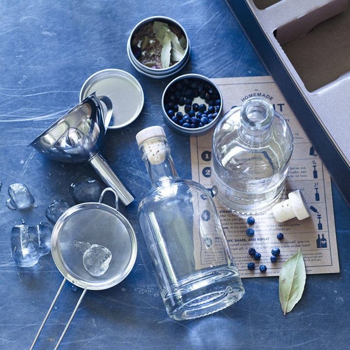 A flatlay of a DIY gin kit on a slate background with empty glass bottles, a funnel, various botanicals (including juniper), ice, and a strainer