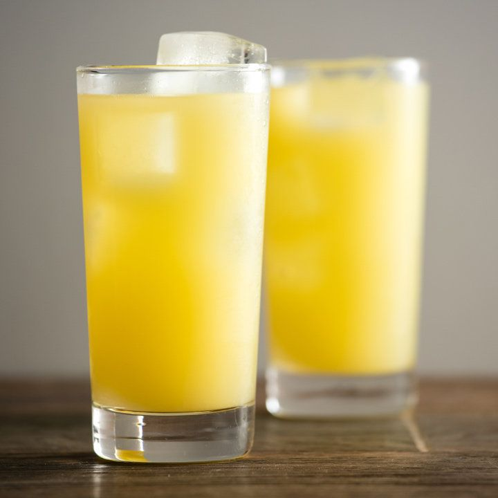 two bright-yellow gin and juice cocktails on a wooden bar