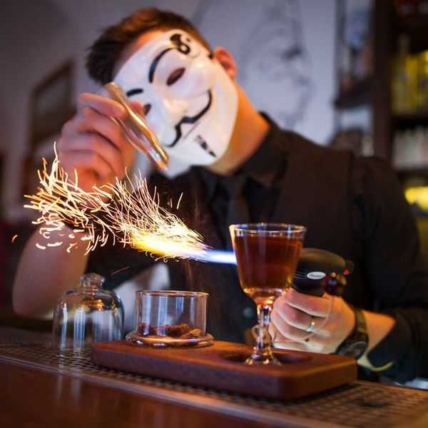 A cocktail at AnonymouS Bar in Prague. The bartender is wearing an Anonymous mask and sparks are coming from a blowtorch near a cocktail glass