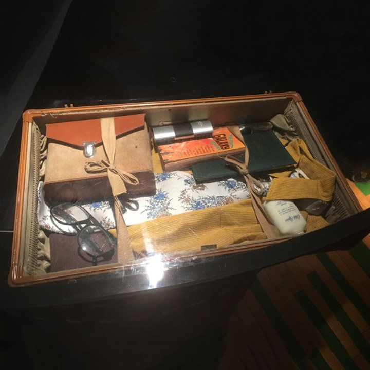 Root Down bar top with a piece of vintage luggage and its contents on full view