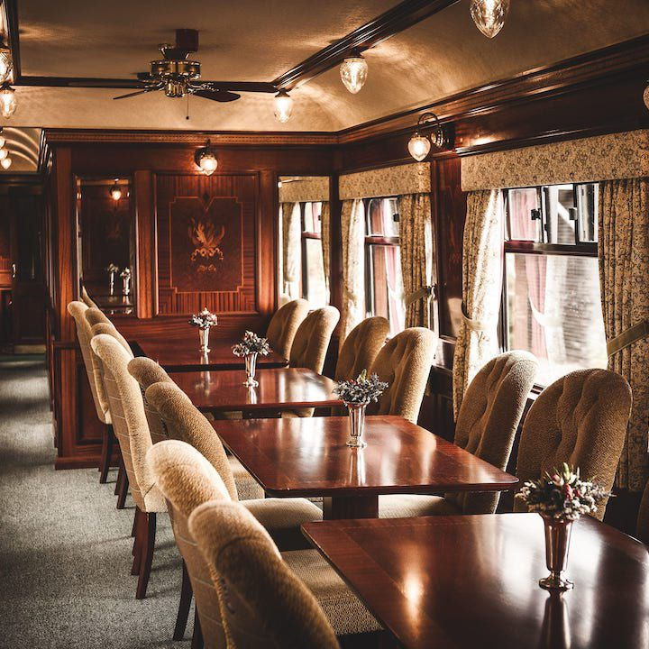Scotch Malt Whisky Tour Train. the inside of a train car shows tufted dining chairs and dark-wood tables