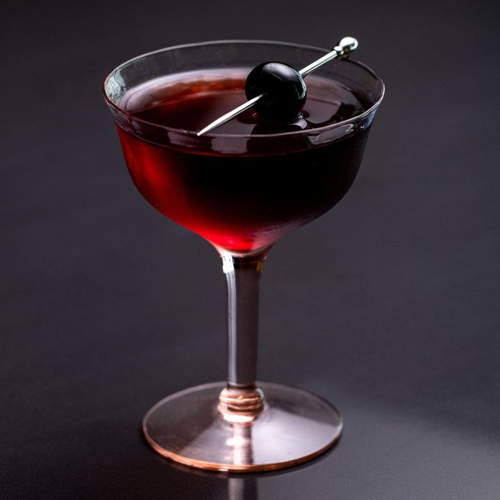 darkside cocktail in a stemmed glass, garnished with a skewered cherry