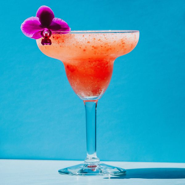 Strawberry Daiquiri in a Margarita glass garnished with an orchid