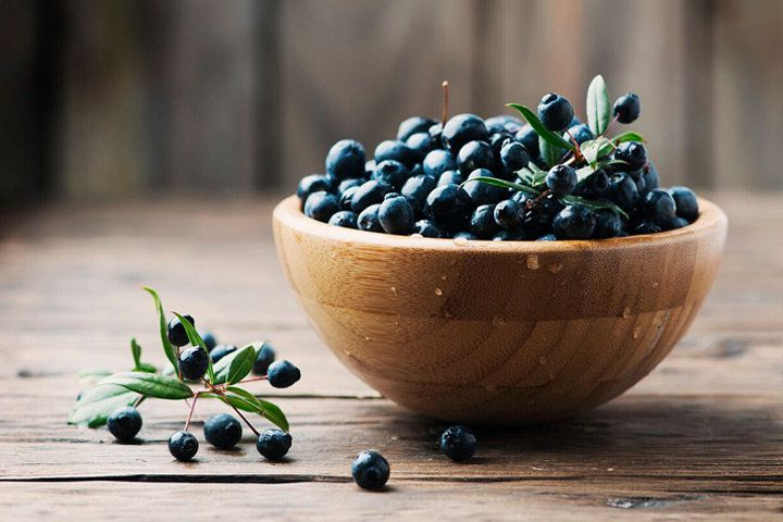 A wooden bowl of dark purple myrtle berries