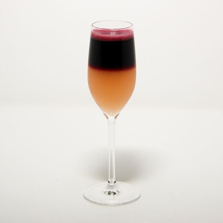 A champagne flute stands on a stark white backdrop. The drink within is layered, with a dark nearly black red floating atop pale orange.