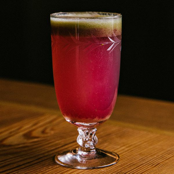 A short-stemmed cocktail glass with leaf etchings sits on a wooden table against an all black backdrop. The glass is filled with a raspberry-hued drink, with a layer of greenish foam settling on top.