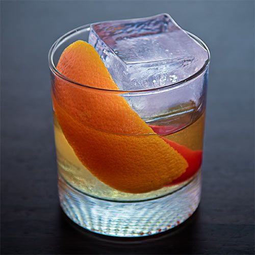 A light amber cocktail on ice in a rocks glass garnished with orange zest and a Fresno chile