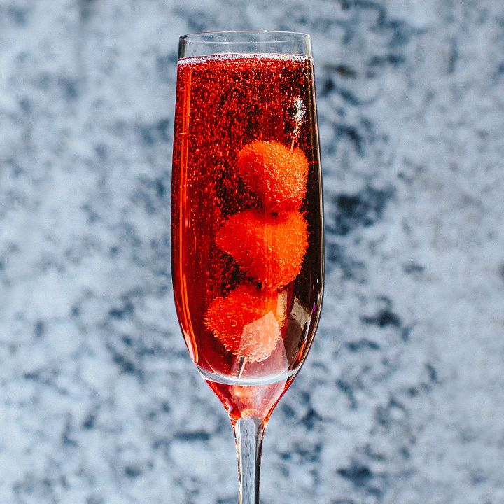 A stemmed Champagne flute bubbles with a crimson colored drink. Three berries on a silver skewer rest in the glass. The background is out of focus gray and blue mottled wallpaper.