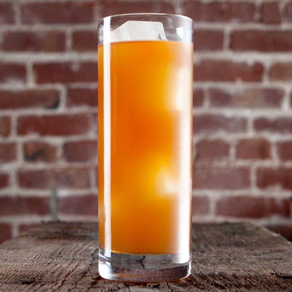 A tall Collins glass sits on a rustic wooden table, a brick wall in the background. The drink within is bright orange and cloudy, with a few large ice cubes floating in it.