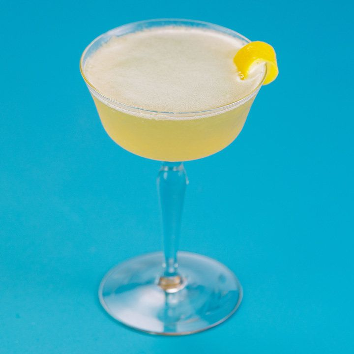 An elegant, thick-stemmed cocktail glass is filled with a hazy yellow drink and garnished with a lemon peel draped over its lip. The background is solid blue.