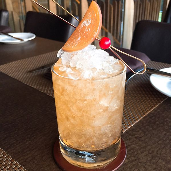 A peach-colored cocktail served in a rocks glass over crushed ice and garnished with a pickled peach slice on a retro wooden pick