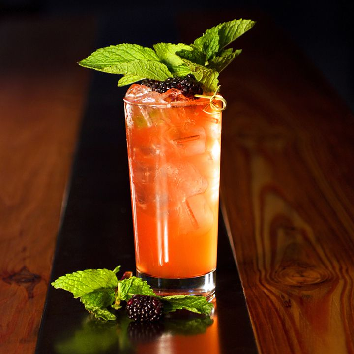 Black-Eyed Rye cocktail in a Highball glass, garnished with mint leaves and three skewered blackberries