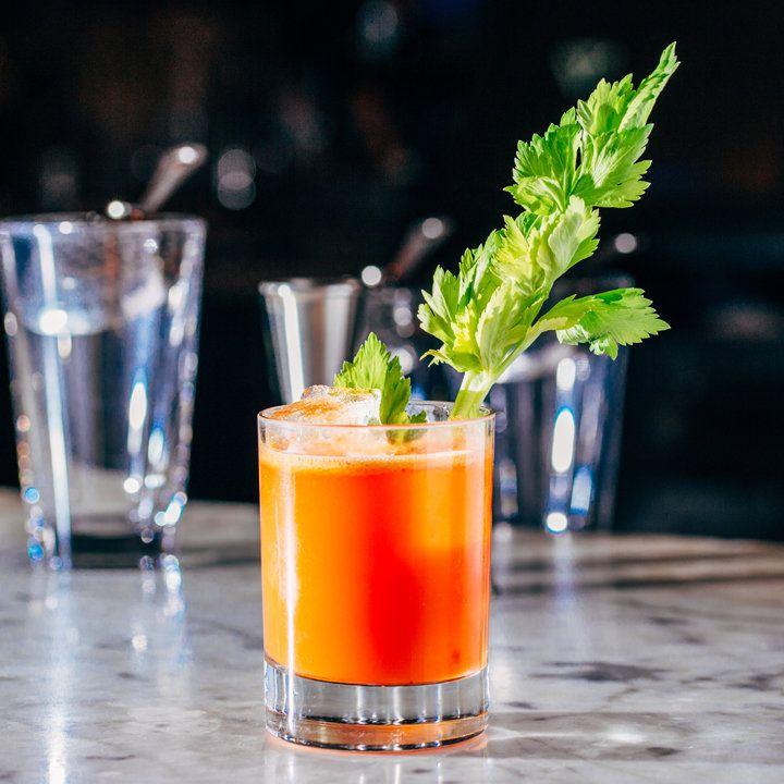 bright-orange Lunar Eclipse cocktail in a rocks glass, garnished with a leafy celery stick and served on a bar in front of glasses and tools