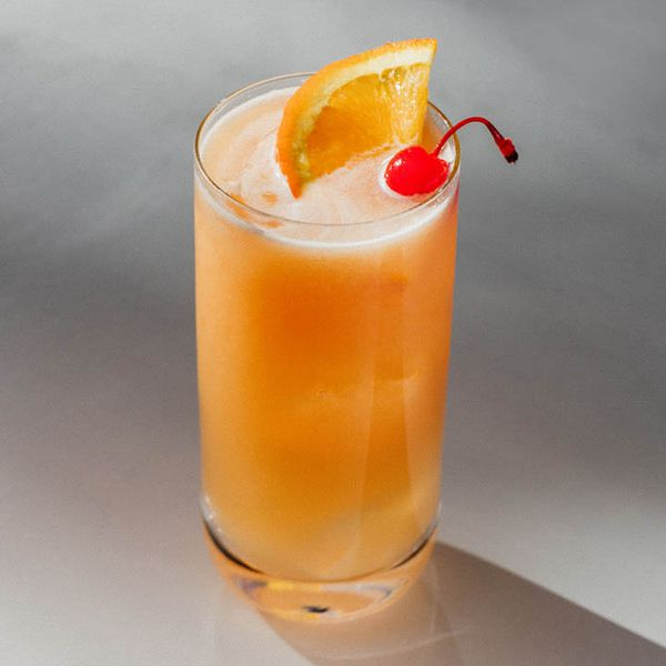 A bright orange-pink cocktail served in a Collins glass and garnished with an orange slice and stemmed candied cherry; the drink is set atop a light gray surface