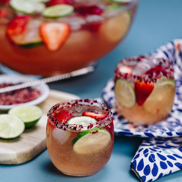 In a busy photo, two short, round glasses are rimmed with rose salt and filled with a bubbly pink punch, strawberries and lime. In the background is the punchbowl with the same drink, and limes and rose salt rest on a cutting board. The background is blue, including a patterned blue and white cloth under one glass.